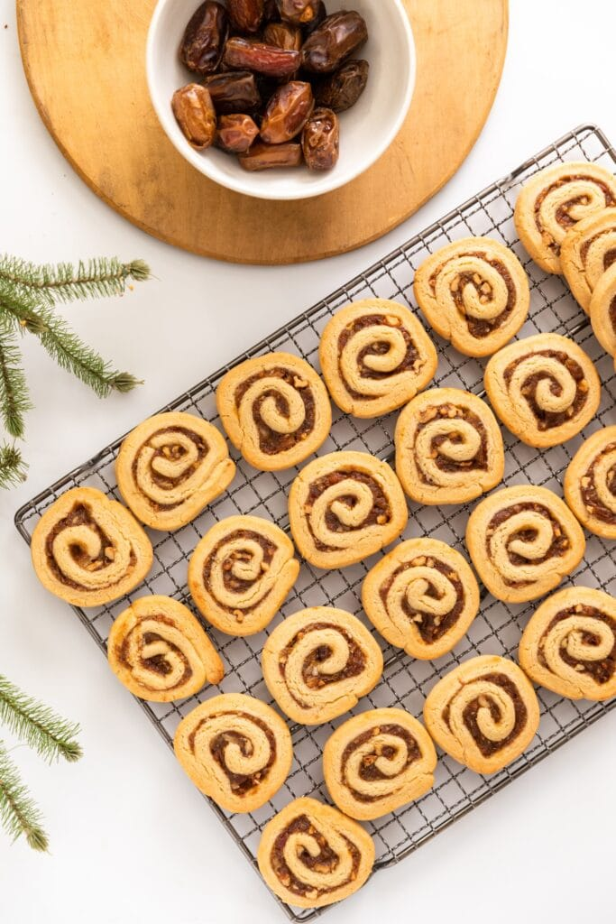 Top down view of entire rack of pinwheel cookies sitting on white surface with wood board and unpitted dates in white bowl
