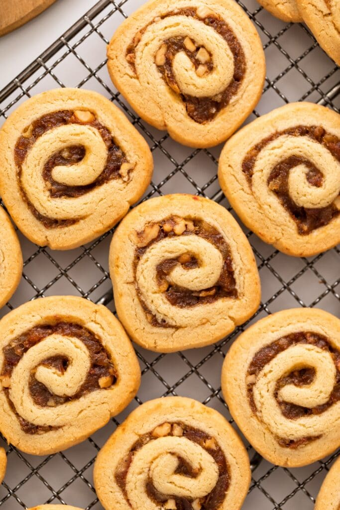 Top down view of golden cookies filled with dates and nuts and rolled in a circle sitting on a cooling rack