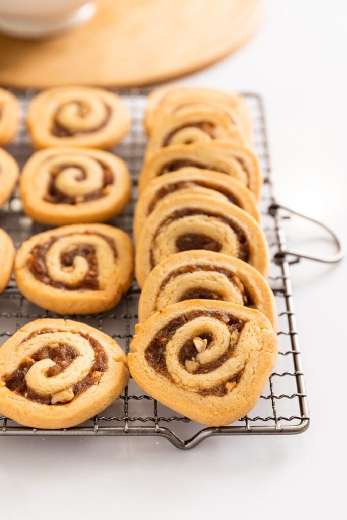 Date nut pinwheel cookies stacked against one another sitting on cooling rack with wood board and white bowl in background