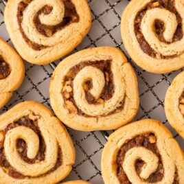 Top down view of pinwheel cookies filled with dates and walnuts sitting on wire cooling rack after coming out of the oven