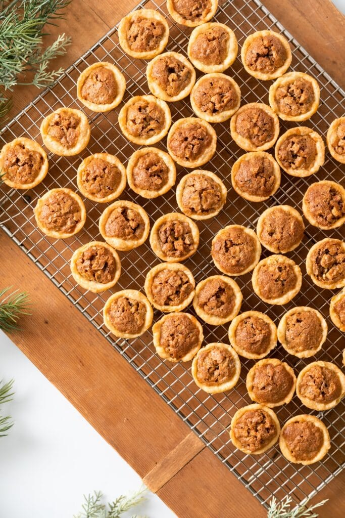 Top down view of many small pecan tassies sitting on cooling rack with wood board underneath with greens nearby