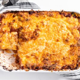 Top down view of white pan holding cheese covered lasagna with rag underneath