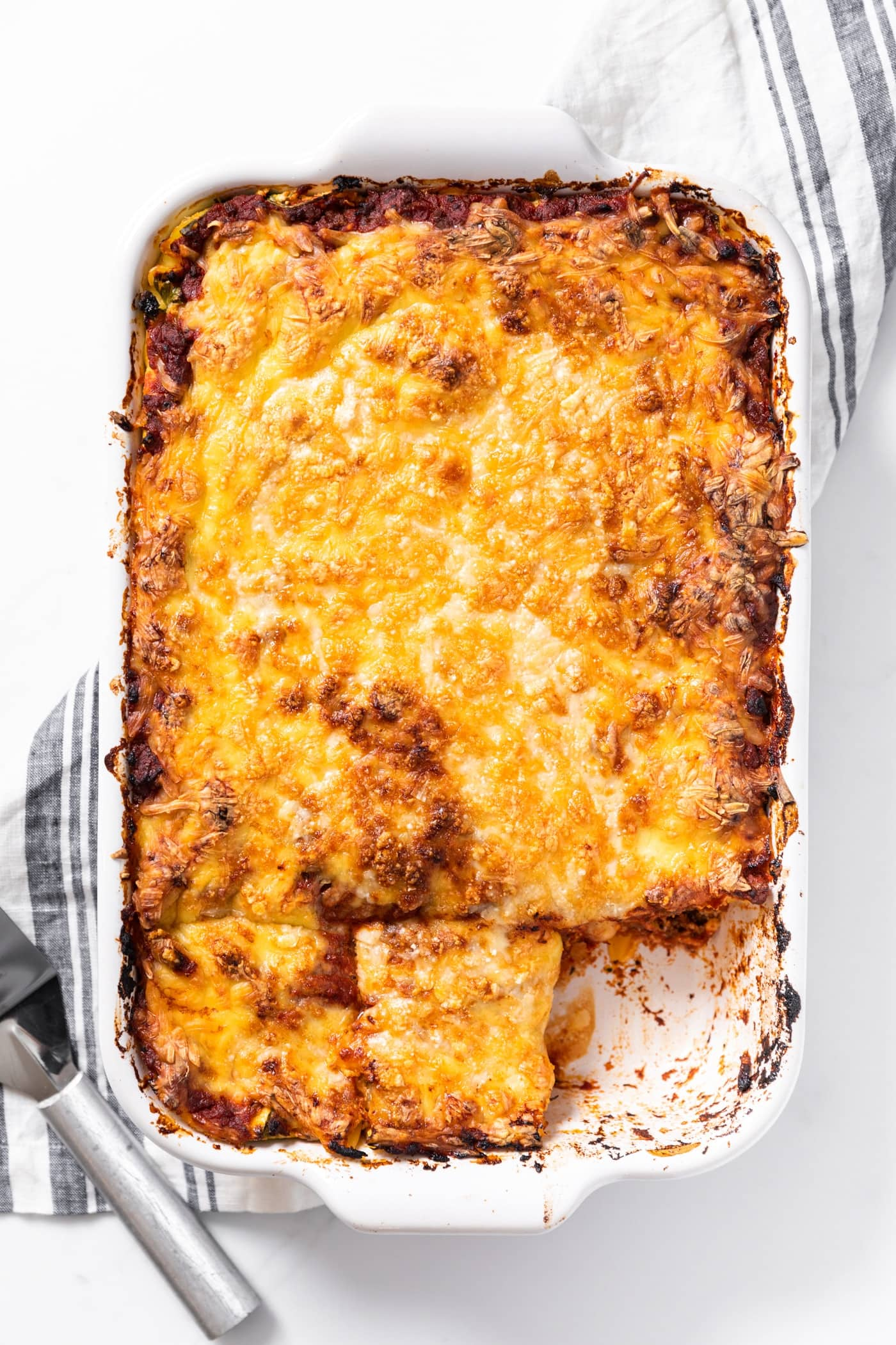 Top down view of large white pan filled with homemade lasagna with golden cheese on top and one piece missing