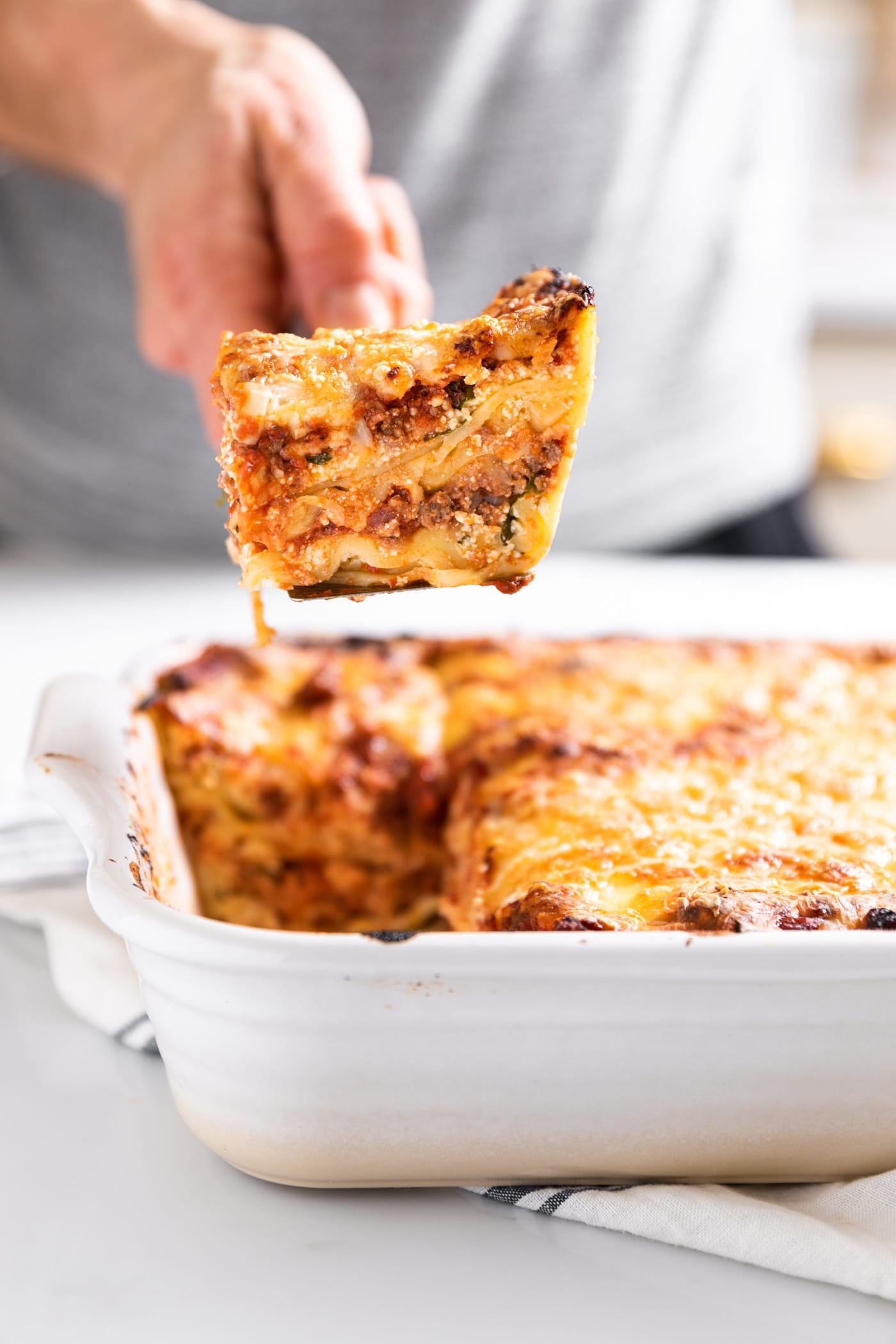 Side view of white pan with lasagna in it with hand holding cut piece above pan