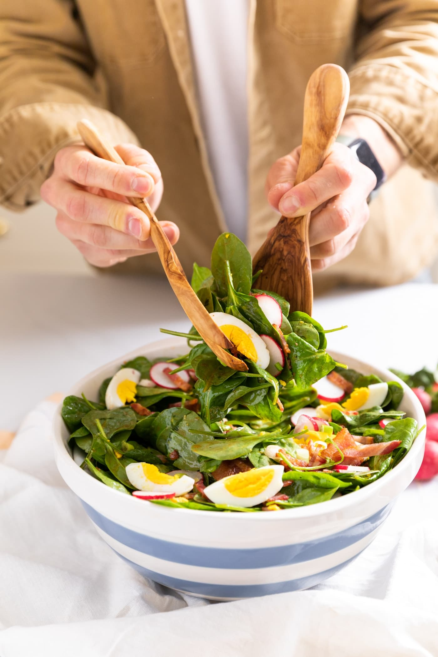 Two hands holding wooden serving spoons taking serving of spinach salad from large white bowl with blue stripes