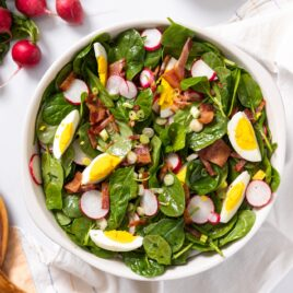 Top down view of spinach pieces in white bowl topped with bacon, eggs, and radish all on white countertop with extra radish