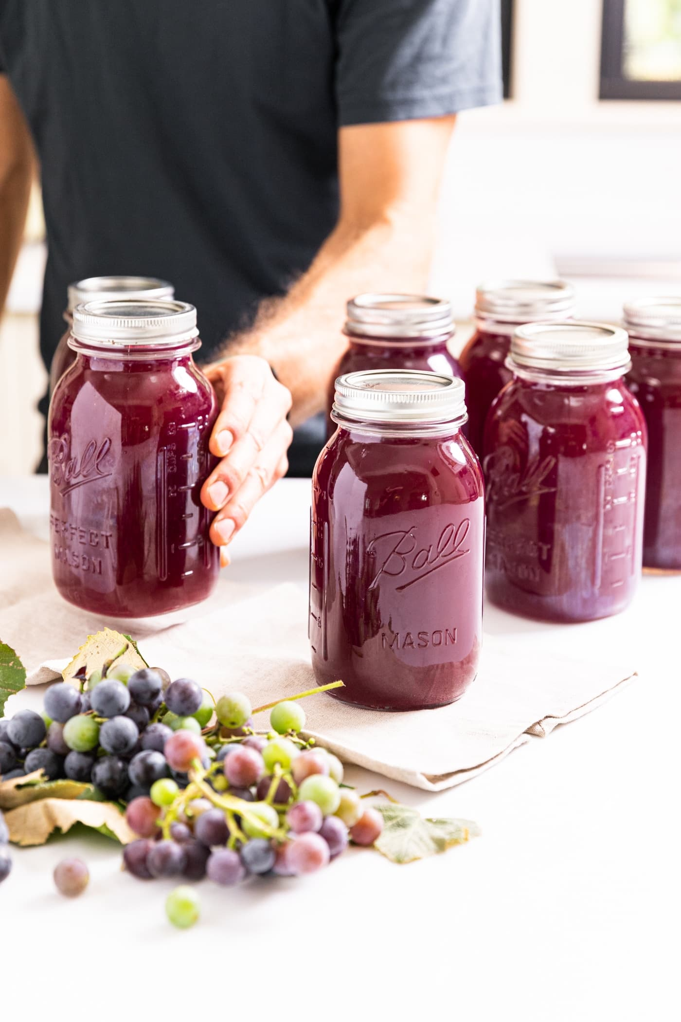 Hand holding glass jar filled with dark purple grape juice concentrate sitting on white countertop with grapes in front