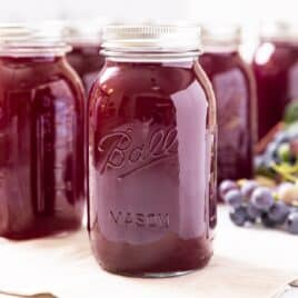Glass jar filled with dark purple grape juice concentrate sitting on white towel with grapes in background behind as well as other glass jars