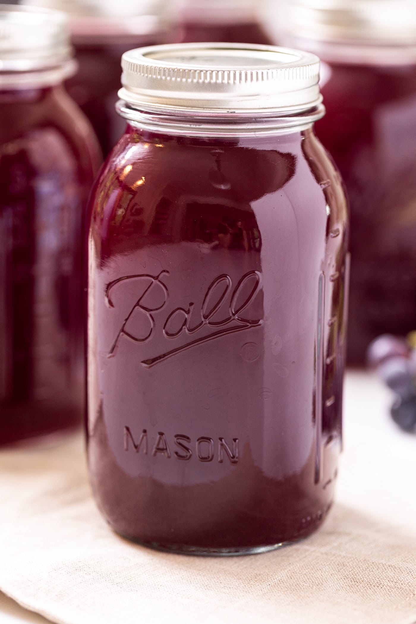 Close up view of large glass container filled with dark purple grape juice concentrate sitting on tan cloth