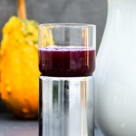 Metal glass filled with grape juice concentrate with gourd and white pitcher in background on a gray slate surface