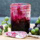 Jar of grape butter sitting on cutting board with knife in front spread with grape butter and grapes to the side all on a piece of gray slate