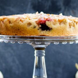 Harvest apple cake with bits of apple and blackberry dotting cake on cake stand with dark gray slate background