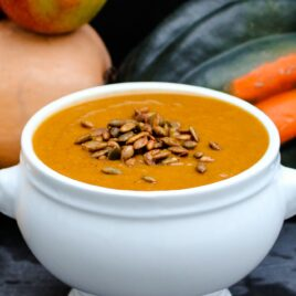 Bowl of orange colored harvest squash soup in white bowl with roasted pepitas on top with apple and various pumpkins and squash against a dark gray background