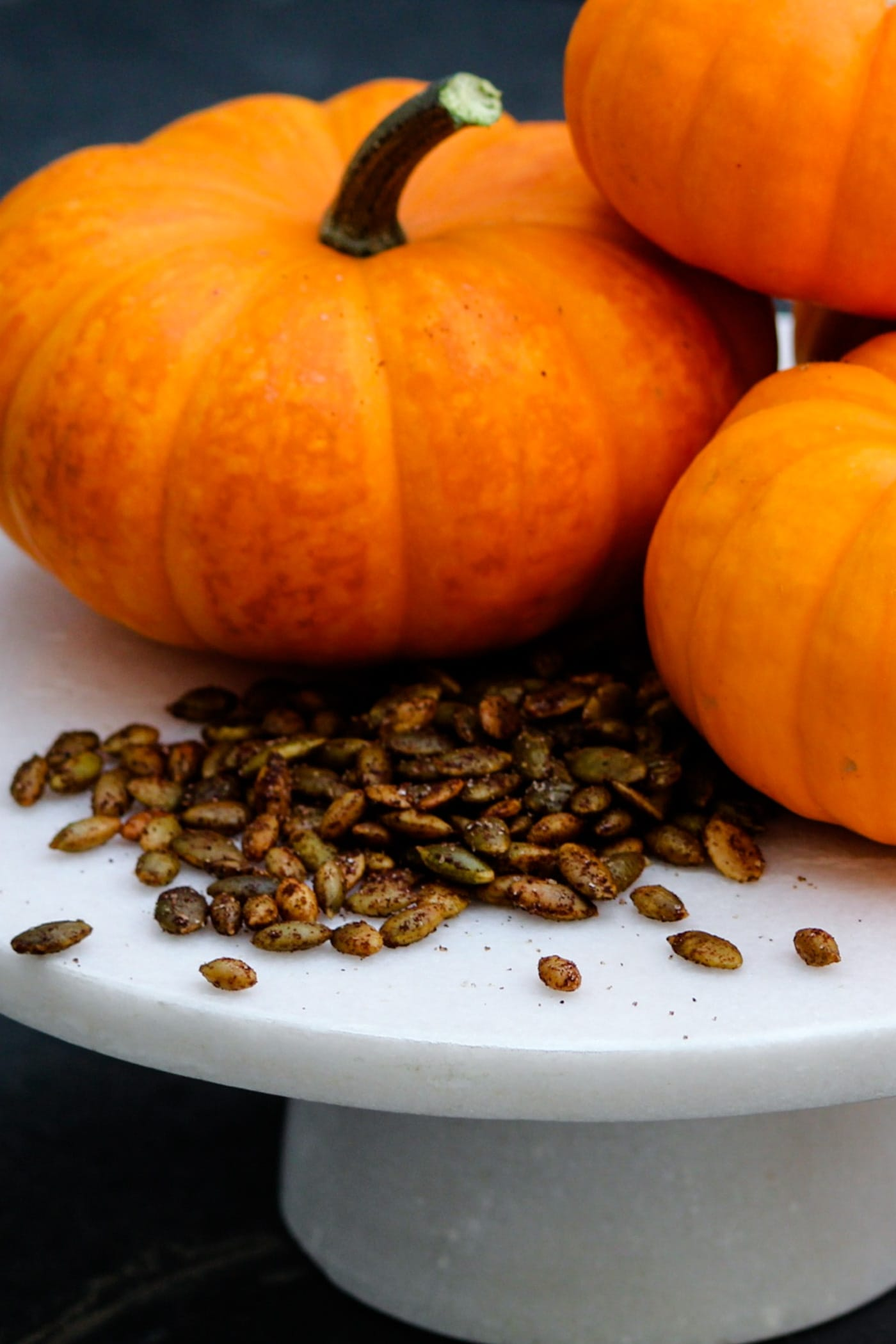 A pile of roasted pepitas sprinkled with spices sitting on a white cake plate with orange pumpkins in background on a dark slate surface