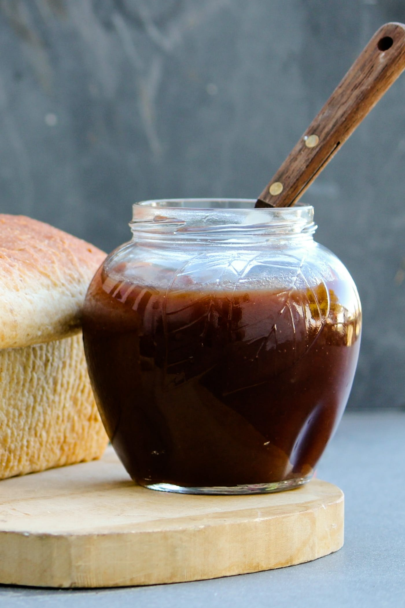 Jar of slow cooker apple butter with loaf of bread beside it and knife sitting on a wood cutting board in front of a gray slate surface