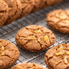 Brown colored molasses crinkle cookie sitting on cooling rack with other cookies stacked around all on white surface