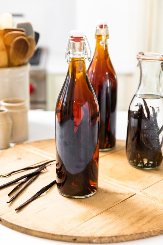 Large narrow bottle sitting on wood board filled with brown colored liquid with vanilla beans sitting beside with bottle with clear liquid behind