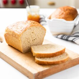 Loaf of sliced bread sitting on cutting board with jam container in background and unsliced loaf in white bread container all on white countertop