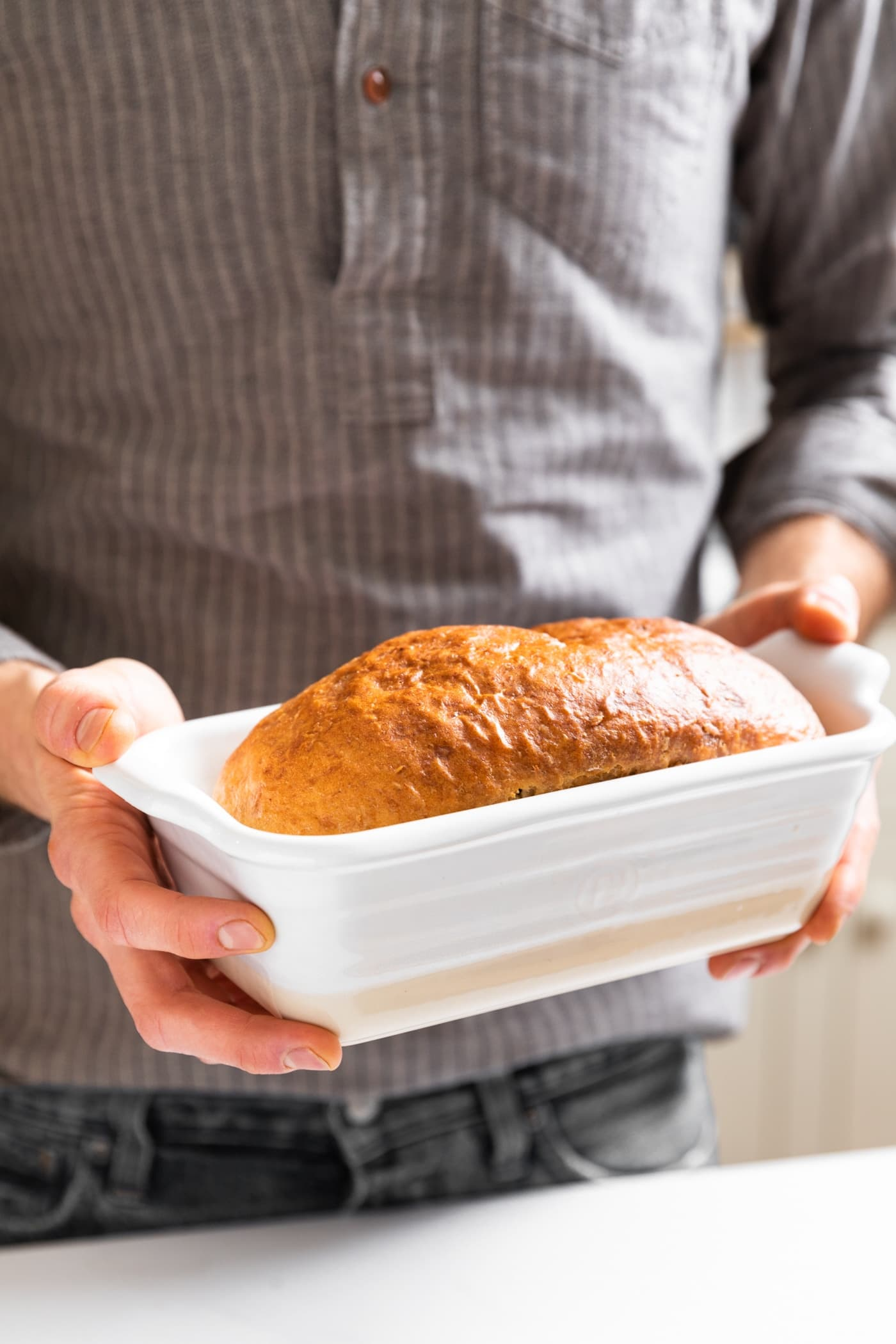Loaf of golden colored bread sitting in white loaf pan being held by person with gray shirt on