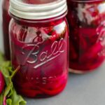 Two jars of dark red pickled beets with extra slices of pickled beets on greens on a gray slate surface