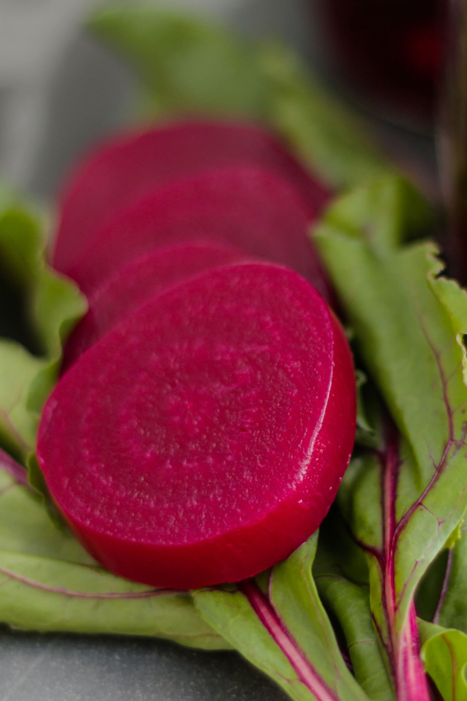 Close up view of slices of dark red pickled beets on a bed of beet leaves on a gray slate surface