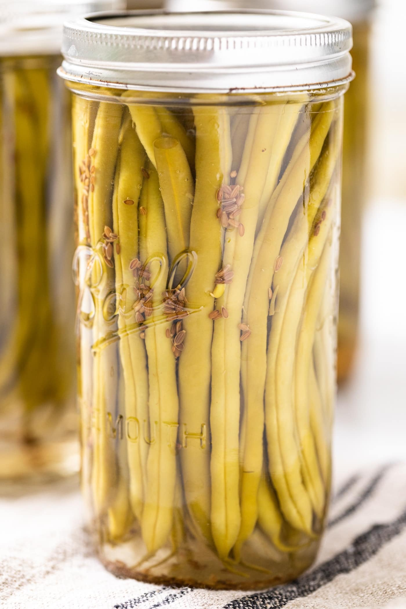 Close up view of glass canning jar filled with green beans with dill seeds floating down the side toward the bottom of the jar