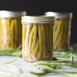 Three jars filled with dilly beans with extra uncooked green beans spread around one white surface with black background