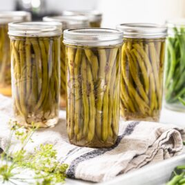 Glass canning jars filled with long green beans with extra glass jars in background and some fresh green beans in foreground