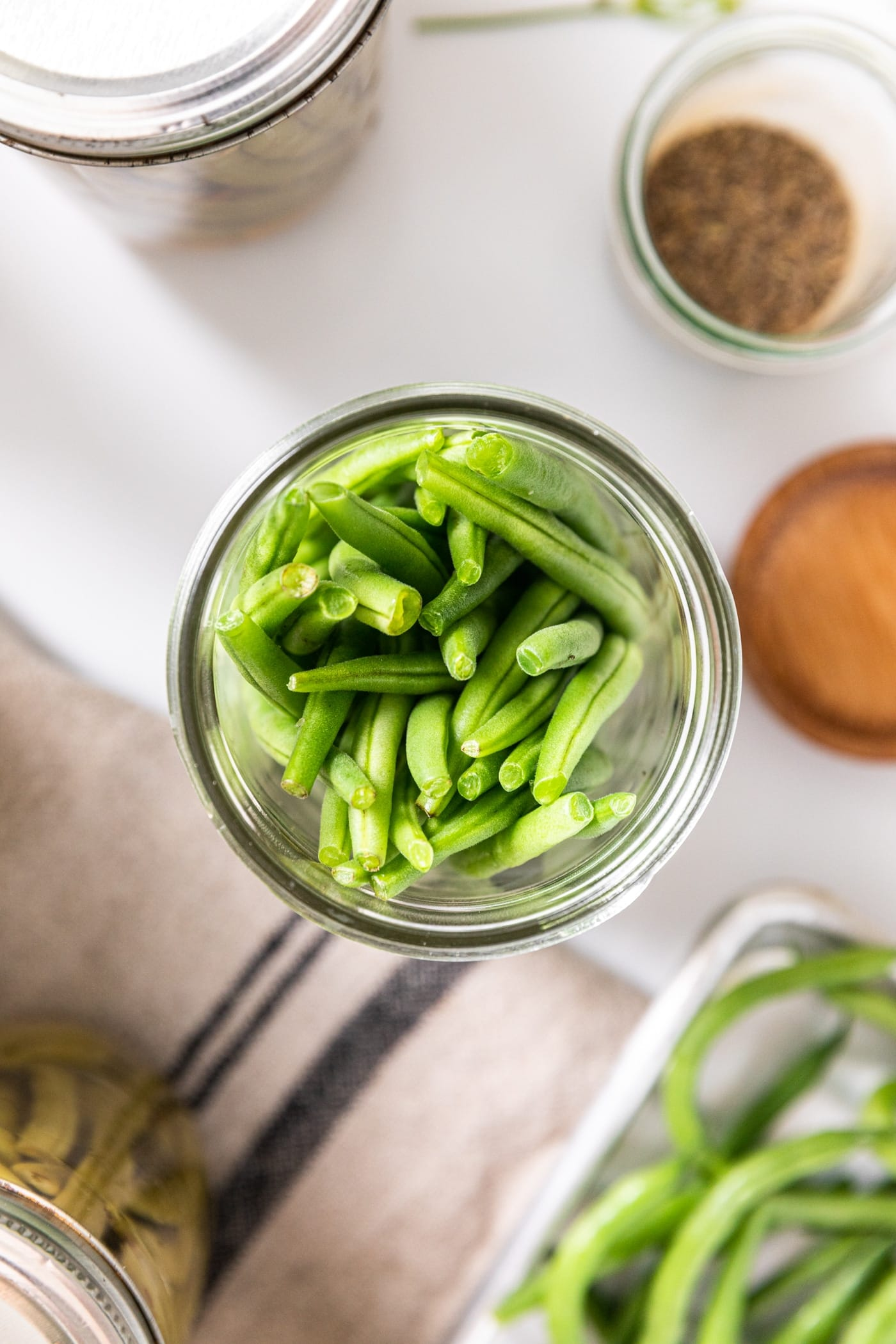 Top down view of glass jar filled with green beans with extra canning supplied all around on white countertop
