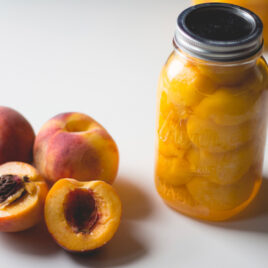 Canned peaches in glass mason jar with lid sitting on white surface with halved peaches cut open