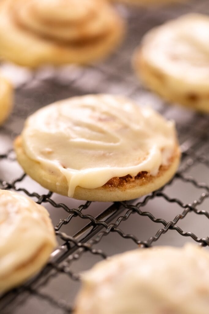 Cinnamon roll cookie with white creamy frosting on top sitting on wire cooling rack with other unfrosted and frosted cookies all around