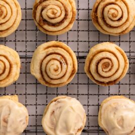 Top down view of little cinnamon roll cookie swirls some with white frosting all sitting on wire cooling rack