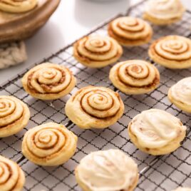 Cinnamon roll cookies with half frosted sitting on wire cooling rack with extra cookies in background along with white container filled with brown sugar