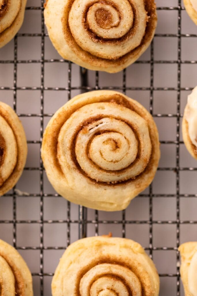 Close up top down view of cinnamon swirled cookies sitting on wire cooling rack with other cookies beside
