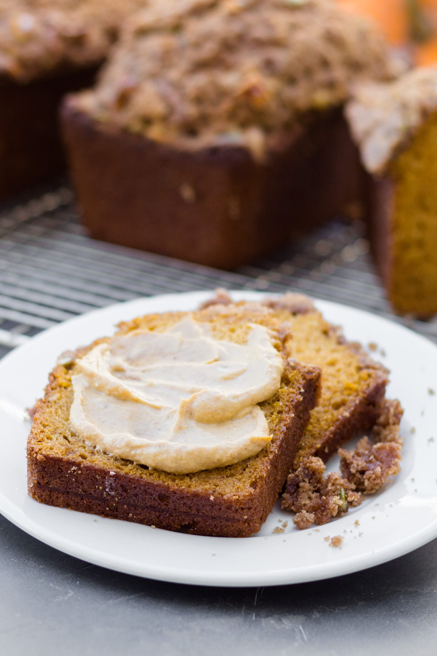 Pumpkin bread spread with pumpkin butter mixture sitting on white plate leaning against cooling rack with additional loaves of bread in background on gray slate surface