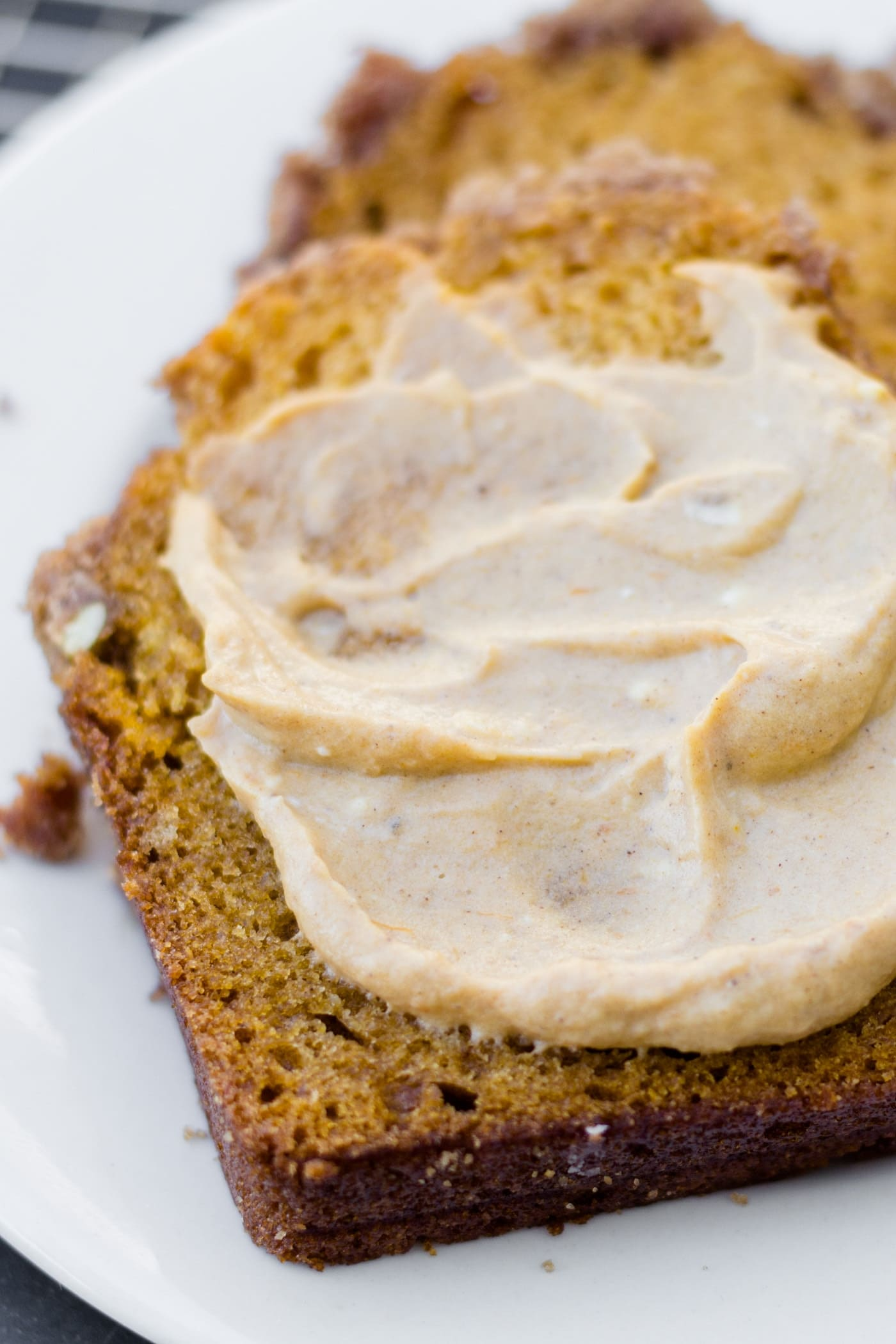Slice of pumpkin bread spread with cream cheese and pumpkin butter mixture sitting on a white plate on a wire cooling rack