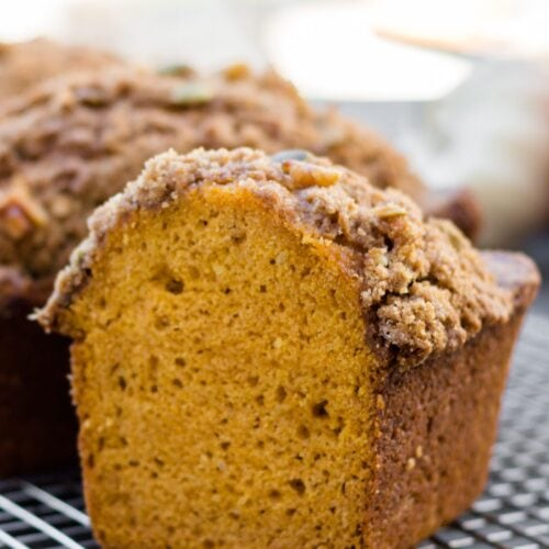 Pumpkin bread sliced in half sitting on cooling rack with additional loaves in background on a gray slate surface