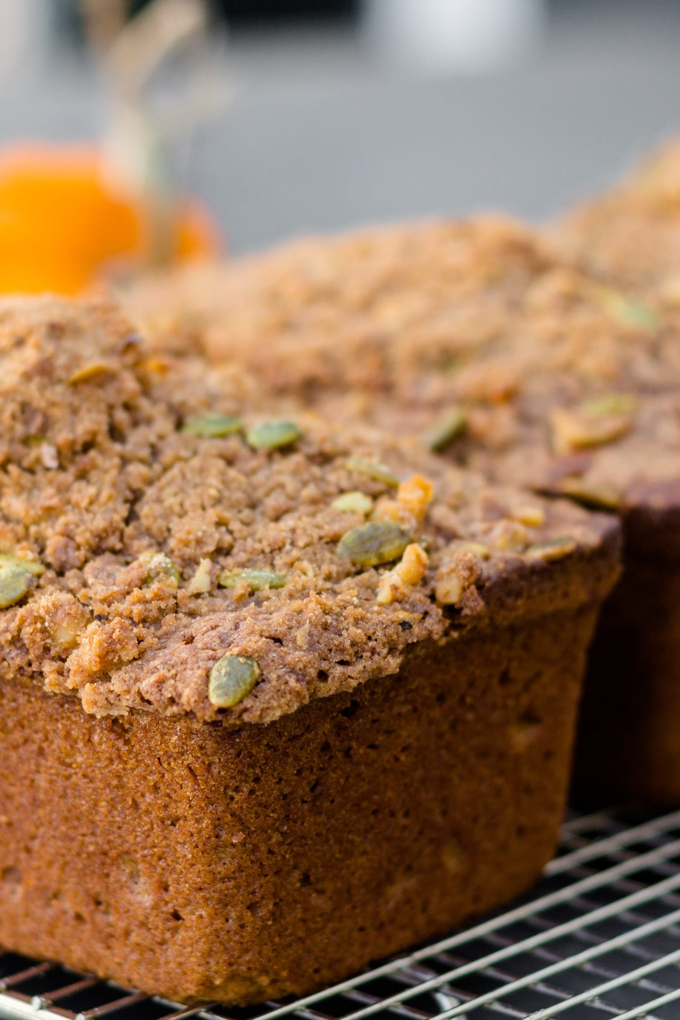 Loaf of pumpkin bread sitting on cooling rack topped with streusel topping with orange pumpkin in background on a gray slate surface