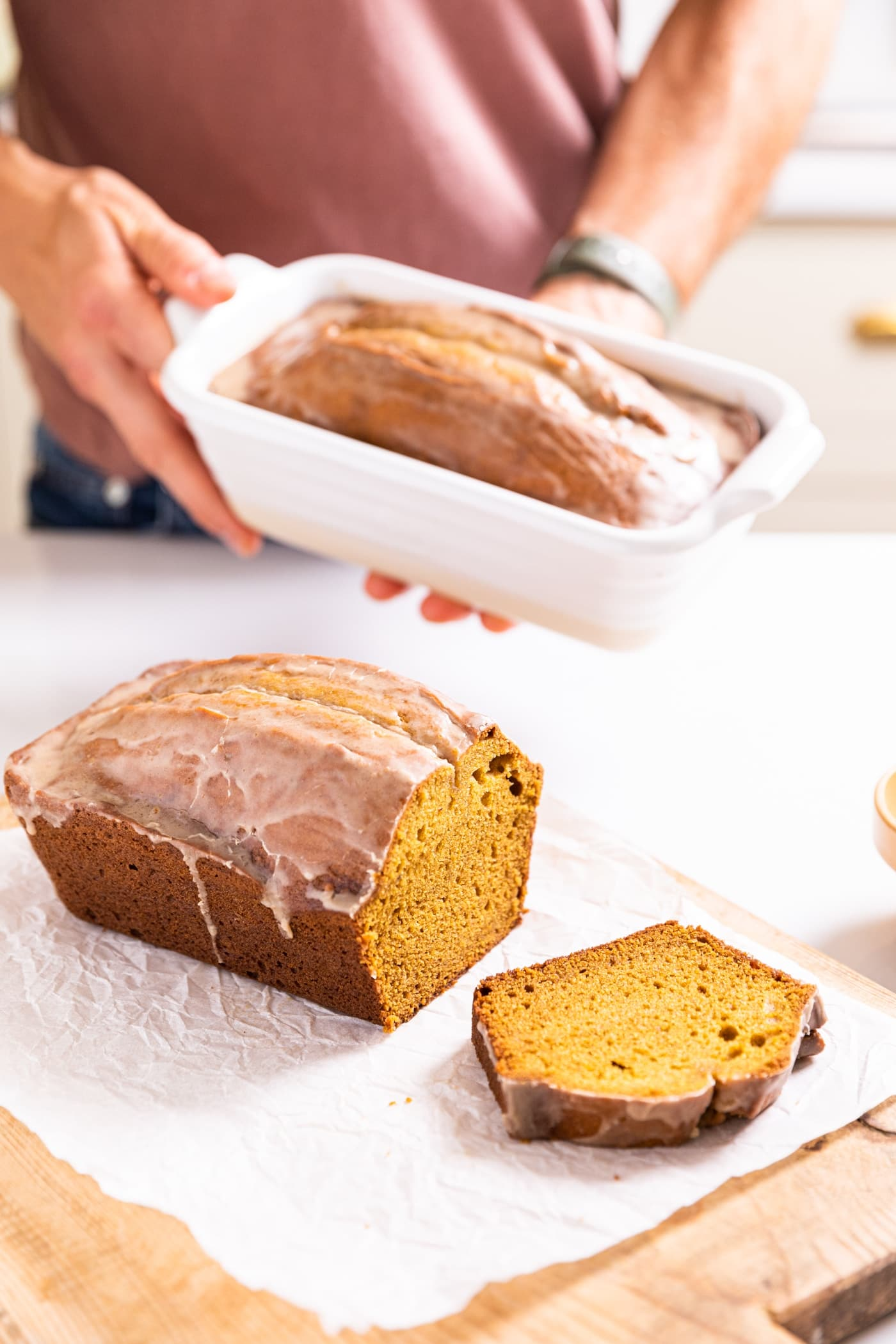 Hand holding pumpkin loaf in white loaf pan with sliced bread in front all on white countertop