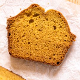 Top down image of slice of pumpkin loaf sitting on crumpled piece of parchment on wood board