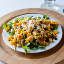 Butternut squash salad on a white plate with brown surface and silverware all on white surface