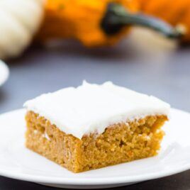 Pumpkin bars sitting on white plate with cream cheese frosting on top on a gray slate surface with orange and white pumpkins in background