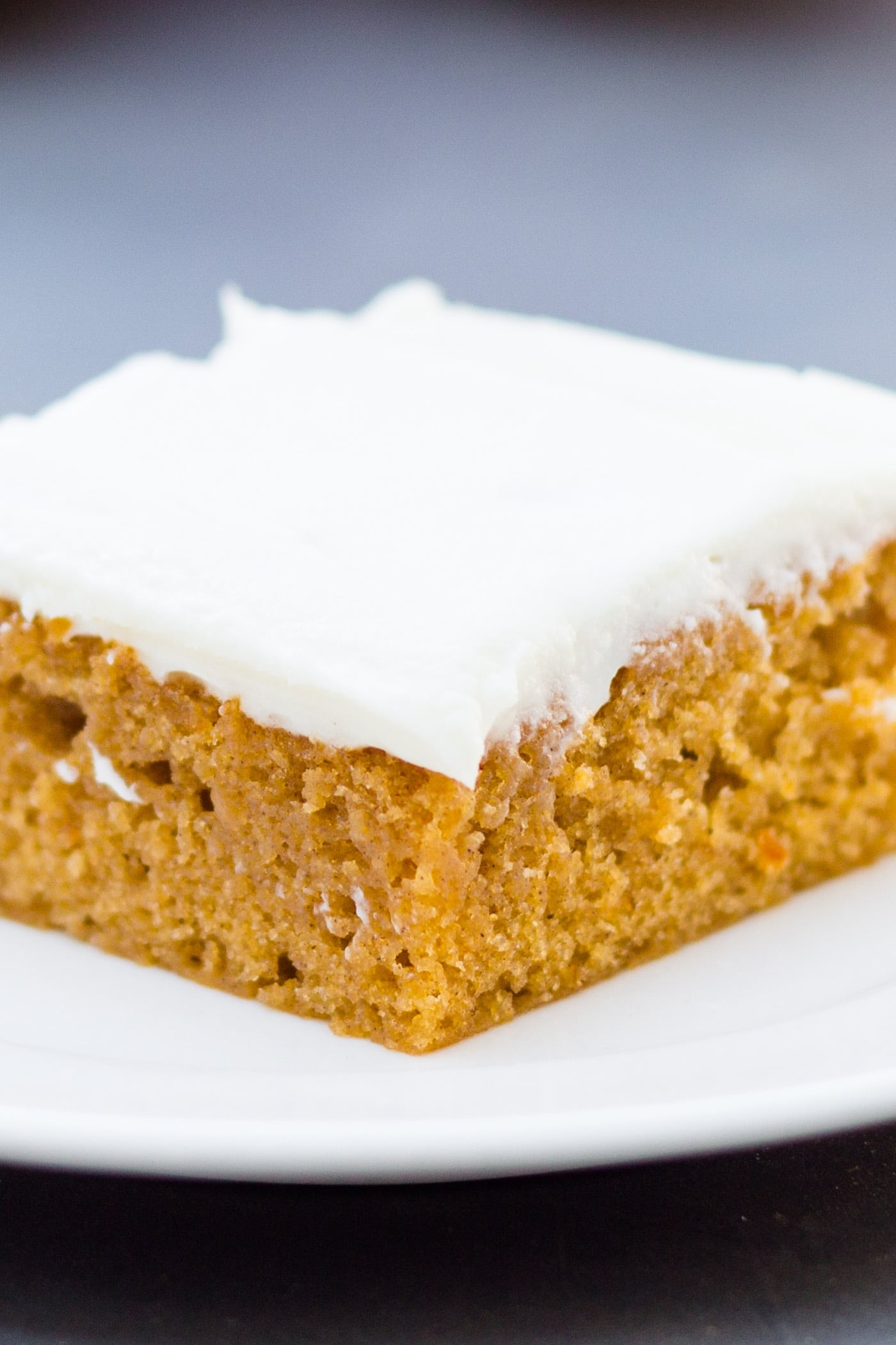 Pumpkin bars sitting on white plate with cream cheese frosting on top on a gray slate surface