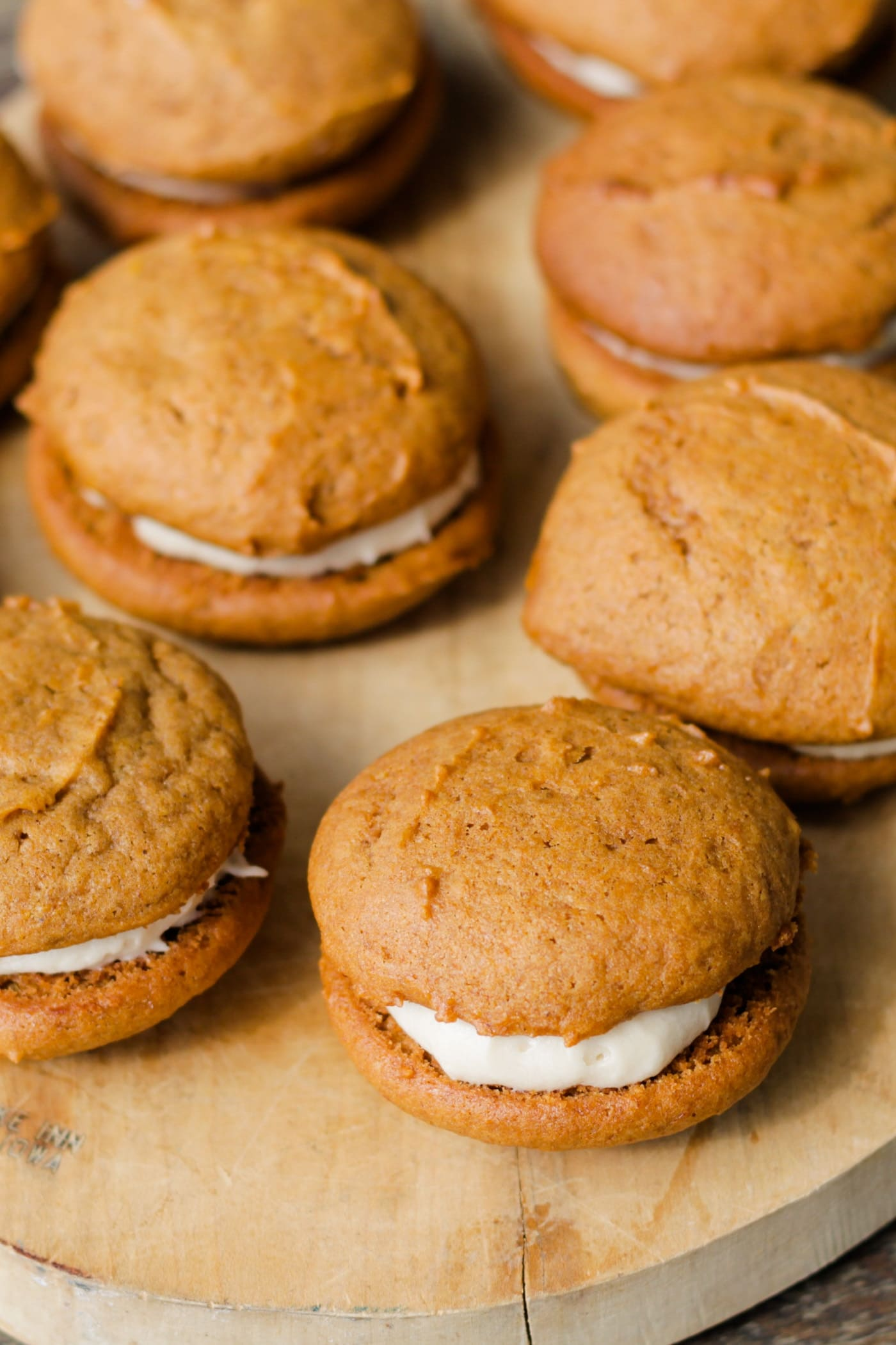 Multiple brown pumpkin whoopie pies with frosting in middle sitting on wood cutting board with extra whoopie pies in background
