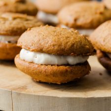 Brown pumpkin whoopie pies with frosting in middle sitting on wood cutting board with extra whoopie pies in background