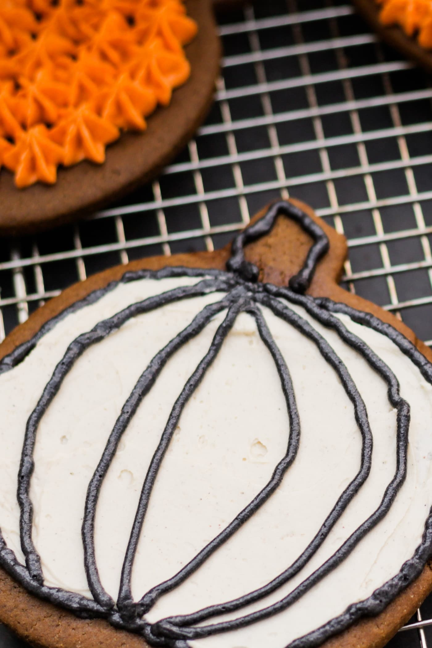 Spiced ginger cutout cookies topped with white frosting sitting on wire cooling rack with extra cookie with orange frosting in background