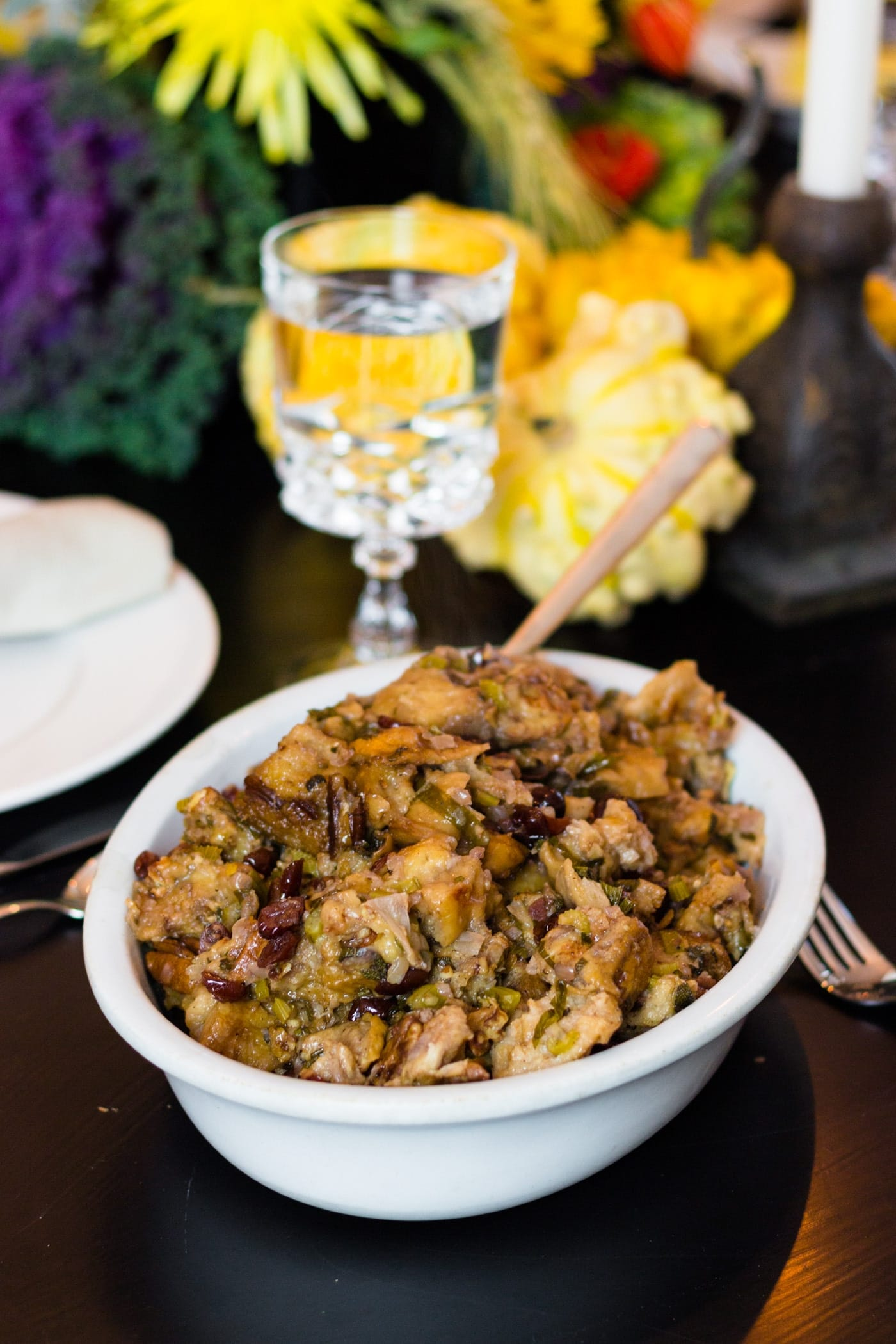 Crock-Pot stuffing in white bowl on a black table set with water glass, extra plates, pumpkins and vibrant flowers
