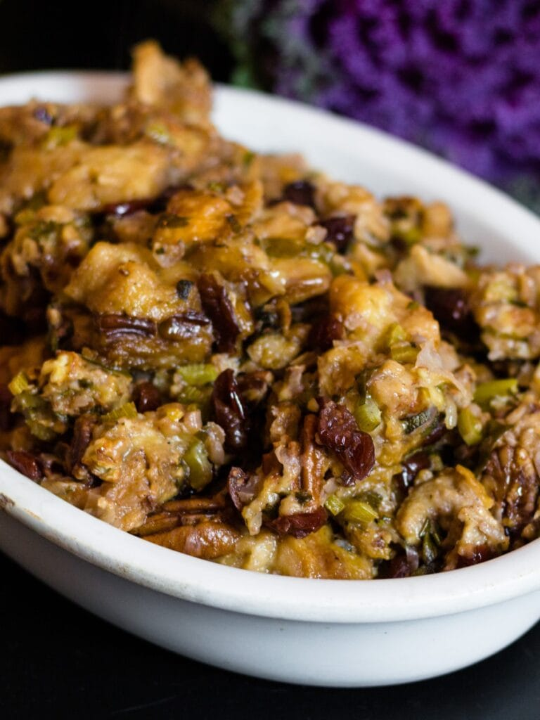 Crock-Pot stuffing in large white bowl sitting on black table with ornamental kale in background