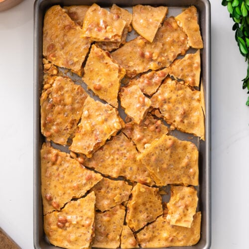 Top down view of shards of yellow colored peanut brittle dotted with peanuts sitting in baking pan all on white marble surface