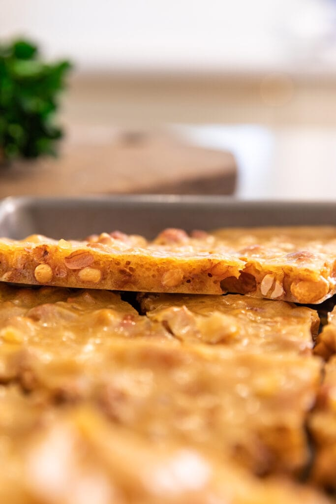 Side view of yellow piece of peanut brittle showing airy pockets with peanuts showing as well sitting on top of other pieces of brittle